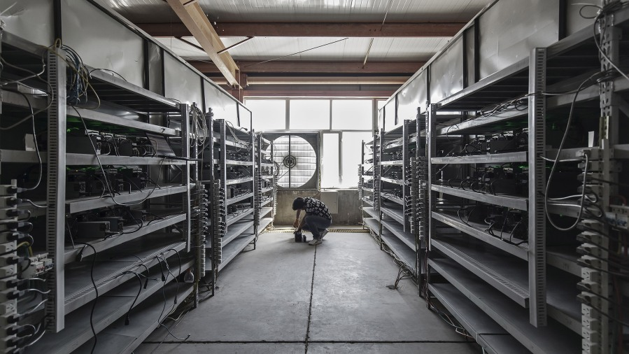 Technician inspects Bitcoin Mining machines.jpg
